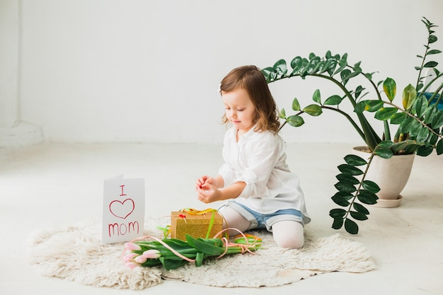 Mädchen, das mit geschenkbox- und tulpenblumen sitzt