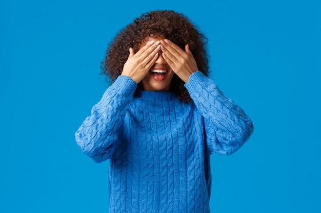 Mädchen, das mit geschwistern im verstecken spielt und zehn zählt, beginnen zu suchen. charismatische reizende afroamerikanerfrau schließt augen als wartende überraschung oder machen peekaboo-geste, blauer hintergrund