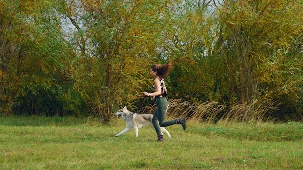 Mädchen, das mit heiserem hund im stadtpark spielt. joggen mit dem hund.
