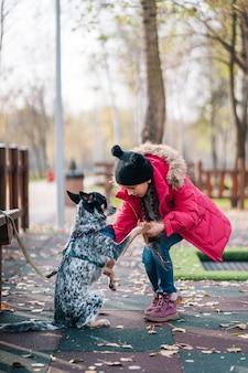 Mädchen, das mit hund im sonnigen herbstpark spielt