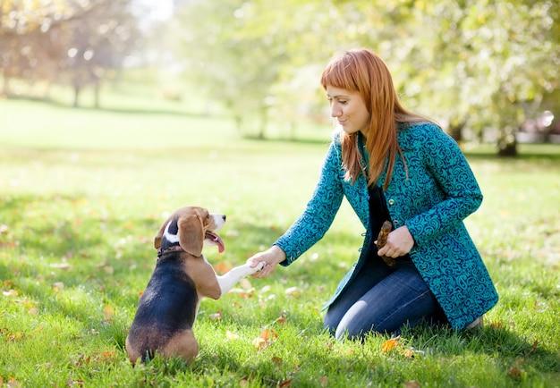 Mädchen, das mit ihrem hund im herbstpark spielt