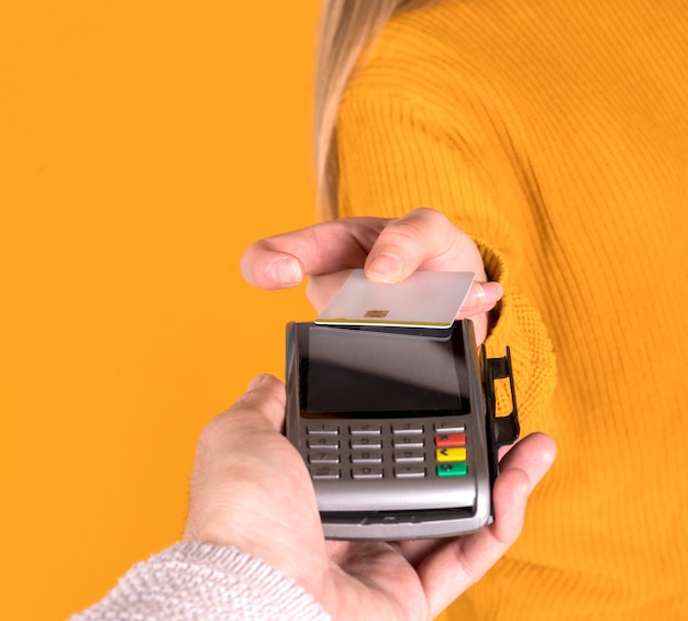 Mädchen, das mit kreditkarte zahlt, online von ihrem smartphone kaufend, gelbe wand
