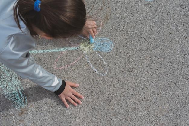 Mädchen, das mit kreide auf straße zeichnet