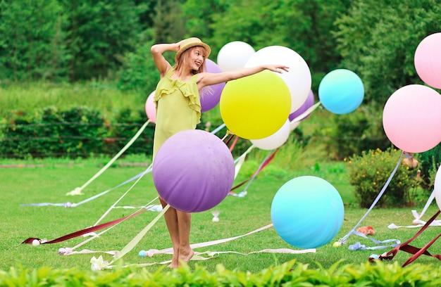 Mädchen, das mit mehrfarbenballonen auf grüner lichtung spielt