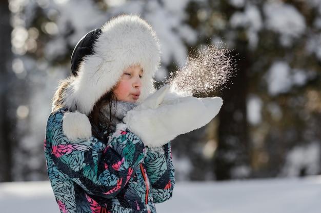 Mädchen, das mit mittlerem schuss des schnees draußen spielt