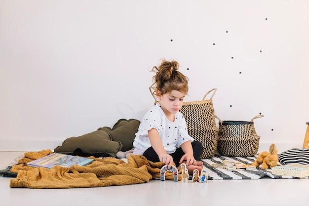 Mädchen, das mit papierspielwaren spielt