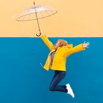 Mädchen, das mit regenschirm springt