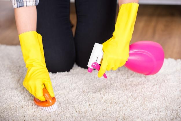 Mädchen, das mit reinigungsmittel spritzt und pinsel über teppich reibt.