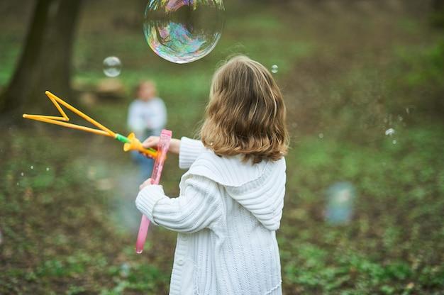 Mädchen, das mit riesiger seifenblase spielt. mädchen, das große luftblasen durchbrennt