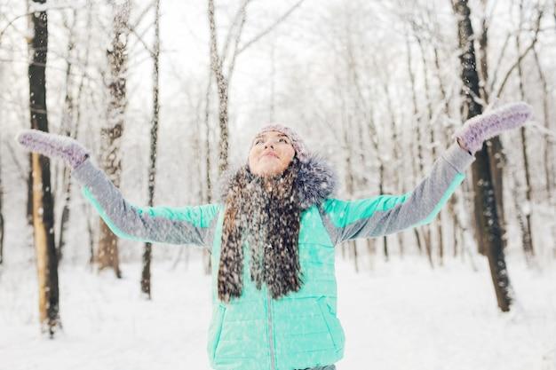 Mädchen, das mit schnee im park spielt. glückliche junge frau, die spaß im schnee hat