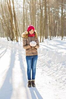 Mädchen, das mit schnee im park spielt. winterzeit