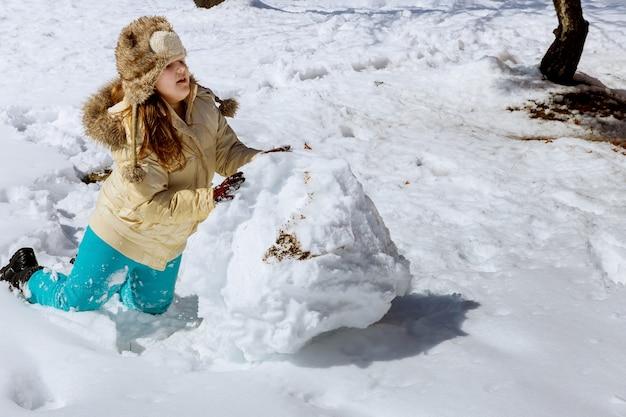 Mädchen, das mit schnee im winter am sonnigen tag spielt