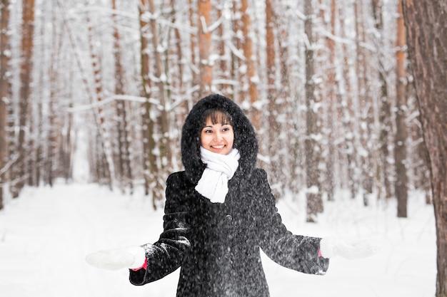 Mädchen, das mit schnee im winterpark spielt.