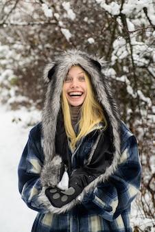 Mädchen, das mit schneemädchen in fäustlingen spielt, halten schneeball winterzeit lächelnde frau in warmer kleidung mit