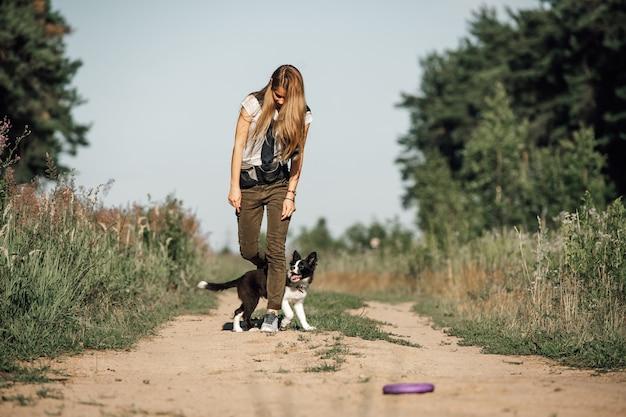 Mädchen, das mit schwarzweiss-randcollie-hundewelpe auf dem waldweg spielt