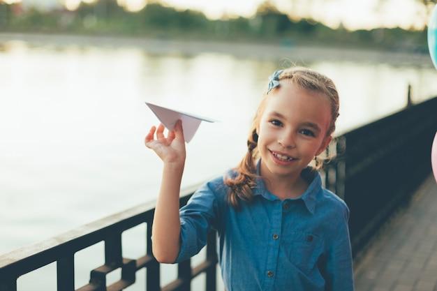 Mädchen, das mit spielzeugpapierflugzeug spielt