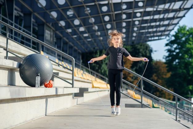 Mädchen, das mit springseil am stadion springt. aktive fitnessfrau, die übungen im freien macht.