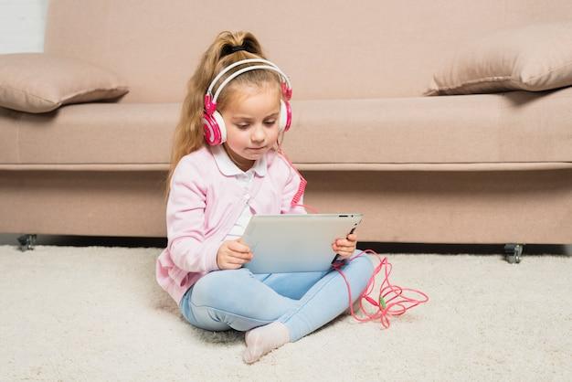 Mädchen, das mit tablette spielt