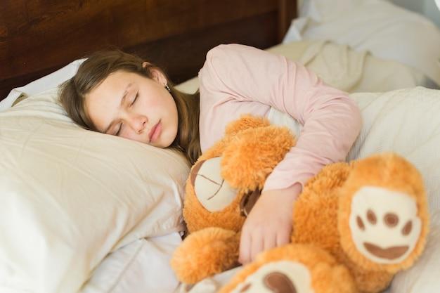 Mädchen, das mit weichem teddybären auf bett schläft