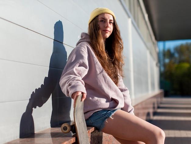 Mädchen, das mittleren schuss des skateboards hält