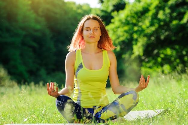 Mädchen, das morgens yoga draußen im wald aufwirft