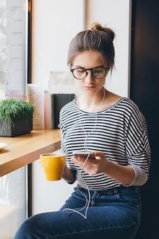 Mädchen, das musik auf ihrem smartphone hört und kaffee trinkt