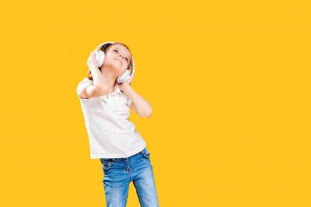 Mädchen, das musik in den drahtlosen kopfhörern hört. tanzendes mädchen. glückliches kleines mädchen, das zur musik tanzt. nettes kind, das glückliche tanzmusik genießt.