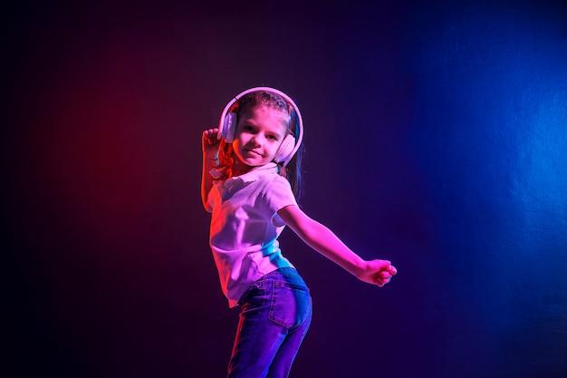 Mädchen, das musik in den kopfhörern auf dunklem buntem hört. neonlicht. tanzendes mädchen. glückliches kleines mädchen, das zur musik tanzt. nettes kind, das glückliche tanzmusik genießt.