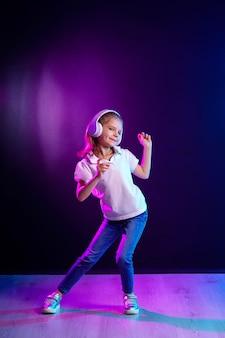 Mädchen, das musik in den kopfhörern auf dunklem buntem hört. tanzendes mädchen. glückliches kleines mädchen, das zur musik tanzt. nettes kind, das glückliche tanzmusik genießt.
