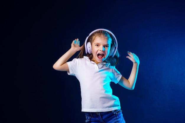 Mädchen, das musik in den kopfhörern auf dunkler bunter wand hört. nettes kind, das tanzmusik genießt,