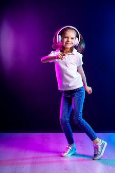Mädchen, das musik in den kopfhörern auf dunkler bunter wand hört. tanzendes mädchen. glückliches kleines mädchen, das zur musik tanzt. nettes kind, das glückliche tanzmusik genießt.