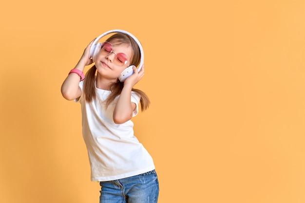 Mädchen, das musik in den kopfhörern auf gelb hört. nettes kind, welches die glückliche tanzmusik, das nahe auge und die lächelnaufstellung genießt