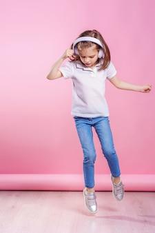Mädchen, das musik in den kopfhörern auf rosa wand hört. tanzendes mädchen. glückliches kleines mädchen, das zur musik tanzt. nettes kind, das glückliche tanzmusik genießt.