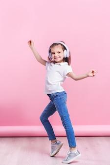 Mädchen, das musik in den kopfhörern einen tanz auf rosa hört. nettes kind, welches die glückliche tanzmusik, das nahe auge und die lächelnaufstellung genießt
