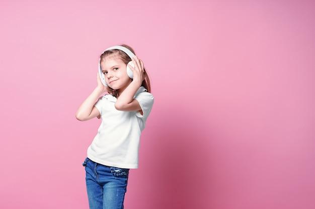 Mädchen, das musik in den kopfhörern hört. nettes kind, welches die glückliche tanzmusik, das nahe auge und die lächelnaufstellung genießt