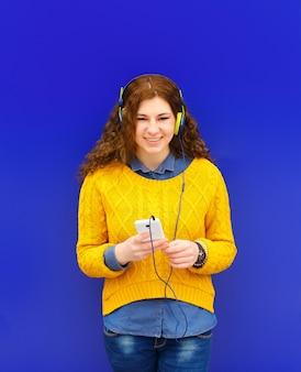 Mädchen, das musik in den kopfhörern mit smartphone hört