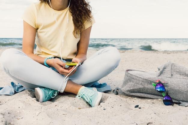 Mädchen, das musik mit kopfhörern auf dem strand hört