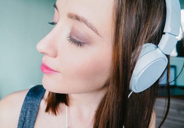 Mädchen, das musik mit kopfhörern mit geschlossenen augen hört