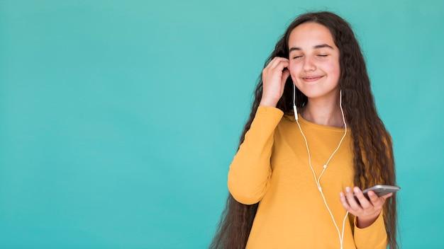 Mädchen, das musik mit kopienraum hört