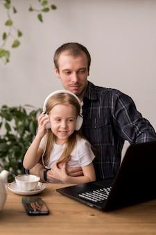 Mädchen, das musik vom laptop an den kopfhörern hört