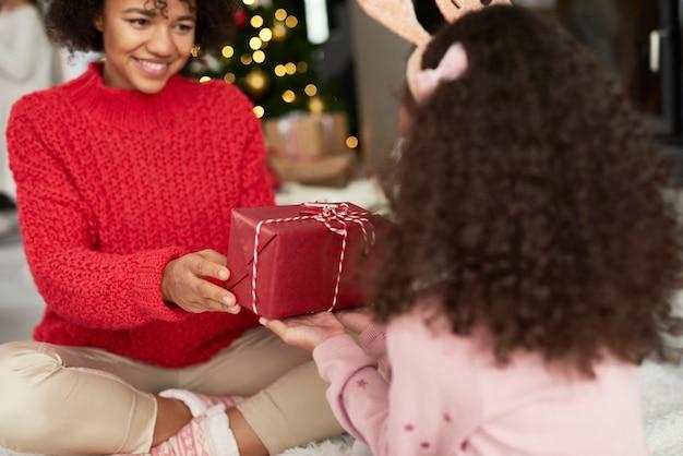 Mädchen, das mutter das weihnachtsgeschenk gibt