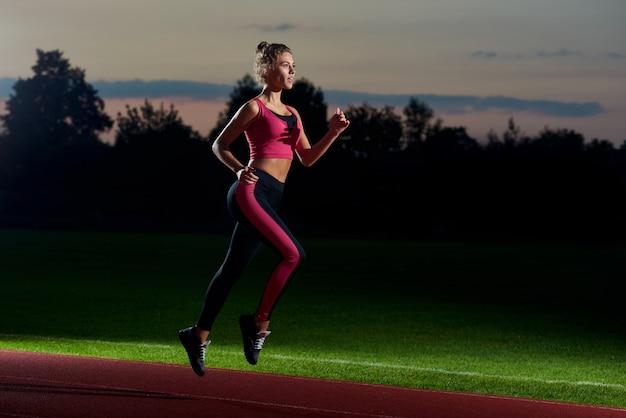 Mädchen, das nachts auf dem stadion sich vorbereitet für marathon läuft.