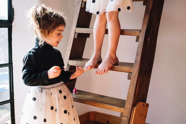 Mädchen, das nagellack auf zehennägel ihrer schwester anwendet