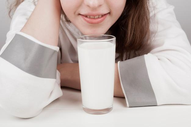Mädchen, das nahe bei einem glas milch bleibt