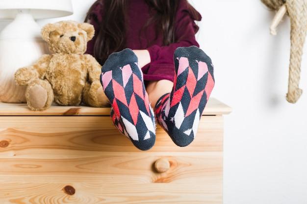 Mädchen, das nahe dem weichen spielzeug zeigt ihre füße mit multi farbigen socken sitzt