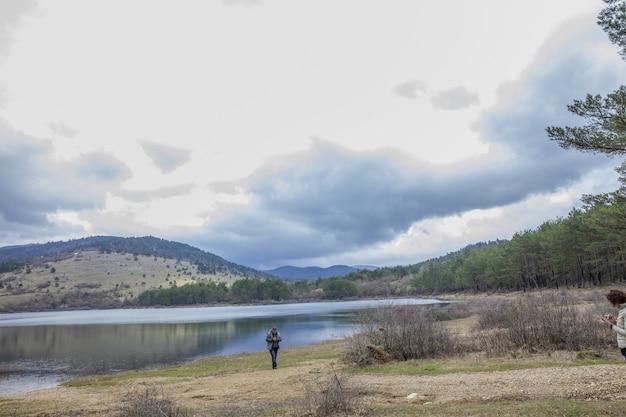 Mädchen, das nahe see piva (pivsko jezero) mit berglandschaft auf der entfernung steht