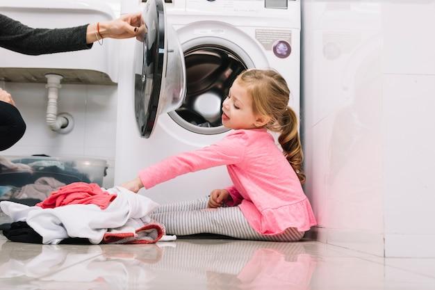 Mädchen, das nahe waschmaschine mit kleidung auf boden sitzt