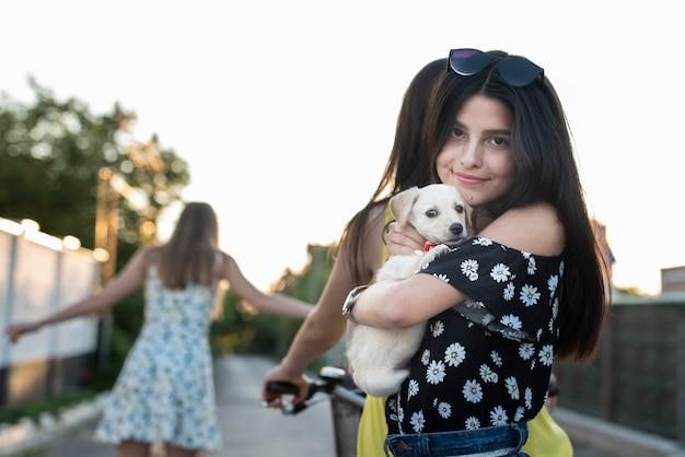 Mädchen, das netten hund umarmt und eine kamera betrachtet