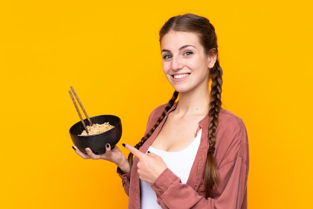 Mädchen, das nudeln über getrennter gelber wand isst
