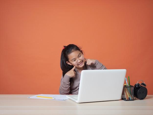 Mädchen, das online mit laptop zu hause studiert